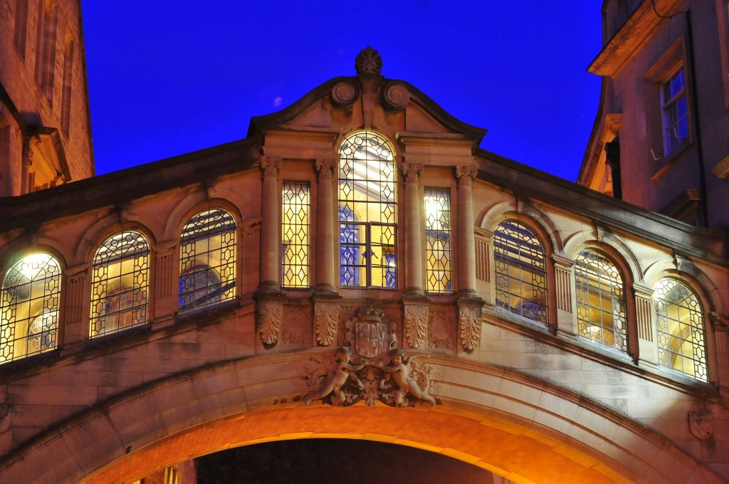 Oxford Bridge of Sighs lit inside againts a blue evening sky