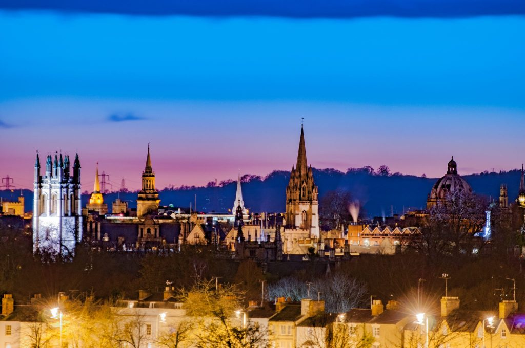 Panorama of Oxford Dreaming Spires with Radcliffe Camera, Magdalen College and St Mary's Church against a pink blue sky at dusk.